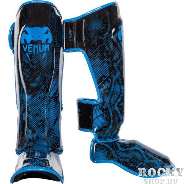 Защита голени Venum Fusion, Синяя VenumЗащита тела<br>Тайские шингарды (накладки на ноги) Venum Fusion. Данный вид шингард предназначен для особо сильной работы ногами, поэтому они пользуются популярностью у бойцов тайского бокса и K-1. Накладки Venum - идеальное сочетание качества, стиля и комфорта. Шингарды надежно защищают и голень, и стопу! Наполнитель: пена, снижающая силу удара. Внешняя обивка: Semi Leather! Все швы тщательно укреплены. Внутренняя обивка: приятная ткань. Великолепно облегают ногу не создавая какого-либо дискомфорт бойцу. Крепятся с помощью двух ремней-липучек. Сделано в Тайланде, ручная работа! Продаются парой.<br><br>Размер: L