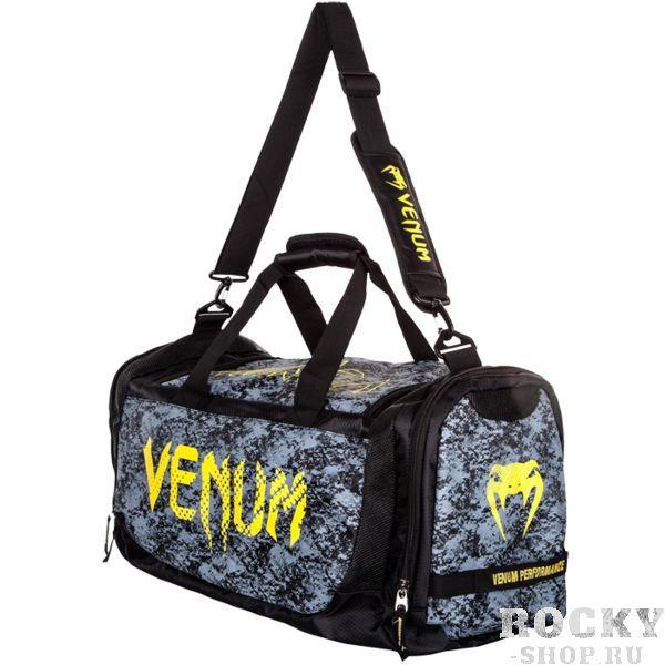 Спортивная сумка Venum Tramo VenumСпортивные сумки и рюкзаки<br>Спортивная сумка Venum Tramo. Она была разработана как универсальное решение для всех борцов и спортсменов - обладает большой вместимостью, приятным дизайном и высокой функциональностью. Она достаточно большая, чтобы вместить помимо всего прочего и Ваши шингарды, и боксерские перчатки! Данная новинка идеальна для переноса всей экипировки сразу, а также она позволяет положить необходимые книги, документы. Кроме того, на боковой части есть специальное отделение для чистой одежды. Сумка выполнена из влагостойкого полиэстера с антимикробной пропиткой. Все ремни и лямки выполнены с учетом всех необходимых эргономических особенностей из мягкой пены и никогда не доставят какого-либо неудобства своему владельцу. К тому же новейшие материалы обеспечивают высокий уровень комфорта. Присутствуют встроенные ручки и ремень для ношения сумки через плечо. Габариты: 68x33x26 см.<br>