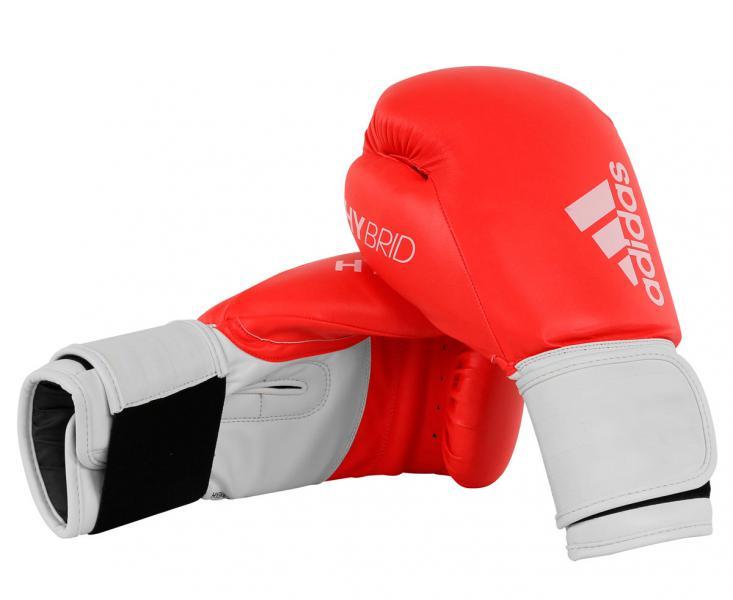 Перчатки боксерские Hybrid 100 красно-белые, 14 унций AdidasБоксерские перчатки<br>Adidas Hybrid 100 ультрановая серия боксерских перчаток. Они изготовлены из полиуретана нового поколения по технологии PU3G INNOVATION.PU3G - этомягкий и прочныйполиуретан, который выглядит, как кожа, и нечувствителен к колебаниям температуры и влажности. ПерчаткаHybrid 100сделана из композитного блока с интегрированным вспененным слоем, придающего перчатке уникальные амортизирующие характеристики. А его эргономичная форма обеспечивает боксеру невероятно удобную посадку перчатки на руке и максимальную безопасность. Перчатка снабжена улучшенной системой липучки для плотной и точной фиксации боксерских перчаток. Крупный логотип adidas и яркая палитра цветов придает перчаткам оригинальный внешний вид.Новыйкомпозитный блокс интегрированным вспененным слоем.Технология PU3GINNOVATION®Оригинальный дизайнИнновационная система закрытияМаксимальная безопасностьПрочная конструкция100% полиуретан.<br>