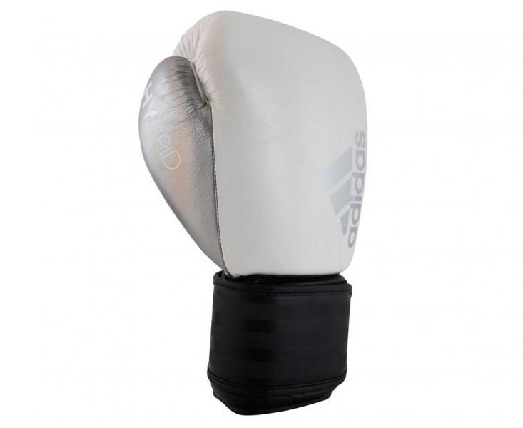 Перчатки боксерские Hybrid 200, 12 унций AdidasБоксерские перчатки<br>Adidas Hybrid 200ультрановая серия боксерских перчаток. Они изготовлены из натуральной кожи высокого качества. Перчатки сделана из композитного блока с интегрированным вспененным слоем, придающего перчатке уникальные амортизирующие характеристики. А его эргономичная форма обеспечивает боксеру невероятно удобную посадку перчатки на руке и максимальную безопасность. Перчатка снабжена улучшенной системой липучки для плотной и точной фиксации боксерских перчаток. Крупный логотип adidas и яркая палитра цветов придает перчаткам оригинальный внешний вид. Новыйкомпозитный блокс интегрированным вспененным слоем. Натуральная кожа высокого качестваОригинальный дизайнИнновационная система закрытияМаксимальная безопасностьПрочная конструкция<br><br>Цвет: бело-черные