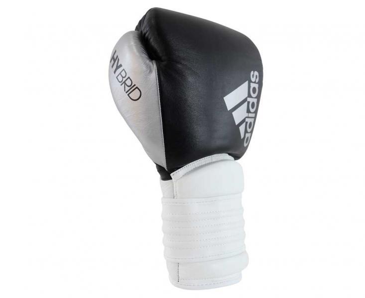 Перчатки боксерские Hybrid 300 черно-белые, 12 унций AdidasБоксерские перчатки<br>Adidas Hybrid 300ультрановая серия боксерских перчаток. Hybrid 300 топовая модель из линейки. Они изготовлены из натуральной кожи высокого качества. Перчатки сделана из композитного блока с интегрированным вспененным слоем, придающего перчатке уникальные амортизирующие характеристики. А его эргономичная форма обеспечивает боксеру невероятно удобную посадку перчатки на руке и максимальную безопасность. Дополнительно усиленный широкий манжет перчатки с интегрированными элементами защиты, исключает риск получения травм кисти. Перчатка снабжена инновационной системой липучки для плотной и точной фиксации боксерских перчаток. Состав: 100% натуральная кожа.Новыйкомпозитный блокс интегрированным вспененным слоем.Натуральная кожа высокого качестваОригинальный дизайнИнновационная система закрытияМаксимальная безопасностьУсиленный манжет.Прочная конструкция<br>
