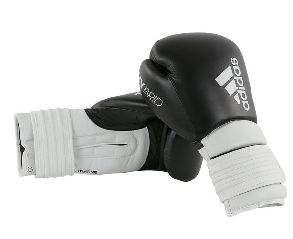 Перчатки боксерские Hybrid 300 черно-белые, 14 унций AdidasБоксерские перчатки<br>Adidas Hybrid 300ультрановая серия боксерских перчаток. Hybrid 300 топовая модель из линейки. Они изготовлены из натуральной кожи высокого качества. Перчатки сделана из композитного блока с интегрированным вспененным слоем, придающего перчатке уникальные амортизирующие характеристики. А его эргономичная форма обеспечивает боксеру невероятно удобную посадку перчатки на руке и максимальную безопасность. Дополнительно усиленный широкий манжет перчатки с интегрированными элементами защиты, исключает риск получения травм кисти. Перчатка снабжена инновационной системой липучки для плотной и точной фиксации боксерских перчаток. Состав: 100% натуральная кожа. Новыйкомпозитный блокс интегрированным вспененным слоем. Натуральная кожа высокого качестваОригинальный дизайнИнновационная система закрытияМаксимальная безопасностьУсиленный манжет. Прочная конструкция<br>