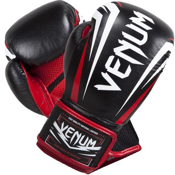 Перчатки для тайского бокса Venum Sharp, 12 oz CombatЭкипировка для тайского бокса<br>Боксерские перчатки Venum Sharp.Эта новинка не оставит равнодушным никого - представляем новые боксерские перчатки от Venum ручной работы.Качество этой новинки просто поражает - отлично обработанные швы, идеально подогнанные друг к другу части перчаток, удобные манжеты, края которых также отстрочены кожей - все это ставит перчатки Шарп в одну линейку с самыми популярными профессиональными моделями.Нужно подчеркнуть, что перчатки сделаны из кожи Nappa.Внутри перчатки наполнены трехслойной анатомической пеной, которая гасит вибрацию от ударов и не дает рукам травмироваться. Защита рук стала бесперецедентной.Также стоит отметить, что в этой модели специалисты Venum отдельно продумали систему фиксации и петель - теперь перчатки сидят как никогда плотно и удобно. При этом внутренняя конструкция и используемые материалы еще лучше отводят влагу. А антибактериальная пропитка не позволит запахам распространиться по всему помещению, в котором вы храните свою экипировку.Большой палец на перчатках зафиксирован - забудьте о возможном скручивании или травмах. Запястье также крепко фиксируется манжетой.Перчатки украшены рельефной эмблемой Venum.Сделаны вручную в Таиланде.<br>