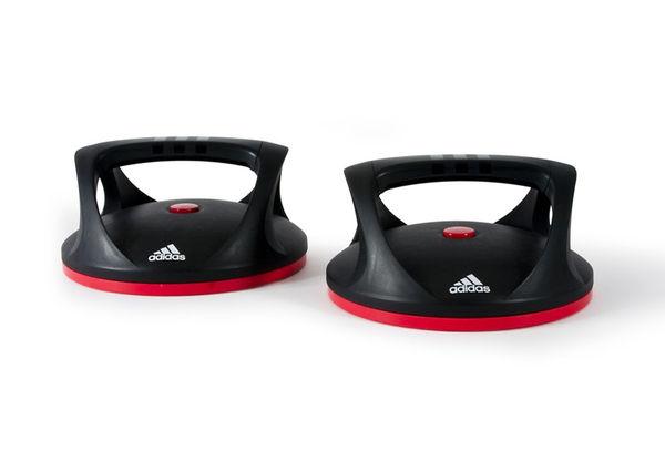 Упоры для отжиманий поворотные Adidas AdidasАксессуары для фитнеса<br>Как можно улучшить такое упражнение какотжимания? Конечно, добавлением вращения. Вращающиеся упоры позволяют вамповорачивать кисти рук в то время, как вы находитесь в нижней позиции приотжиманиях. Это вызывает большее напряжения мышц груди и плеч по сравнению собычными отжиманиями.<br>