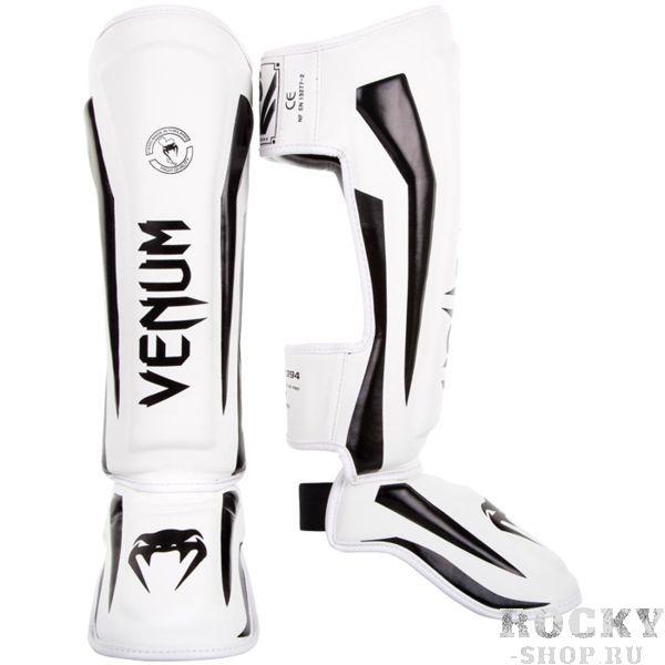 Шингарды Venum Elite VenumЗащита тела<br>Тайские шингарды (накладки на ноги) Venum Elite. Данный вид шингард предназначен для особо сильной работы ногами, поэтому они пользуются популярностью у бойцов тайского бокса и K-1. Накладки Venum - идеальное сочетание качества, стиля и комфорта. Шингарды надежно защищают и голень, и стопу! Наполнитель: пена, снижающая силу удара. Внешняя обивка: Skintex Leather! Все швы тщательно укреплены. Внутренняя обивка: приятная ткань. Великолепно облегают ногу не создавая какого-либо дискомфорт бойцу. Крепятся с помощью двух ремней-липучек. Сделано в Тайланде, ручная работа! Продаются парой.<br><br>Размер: L