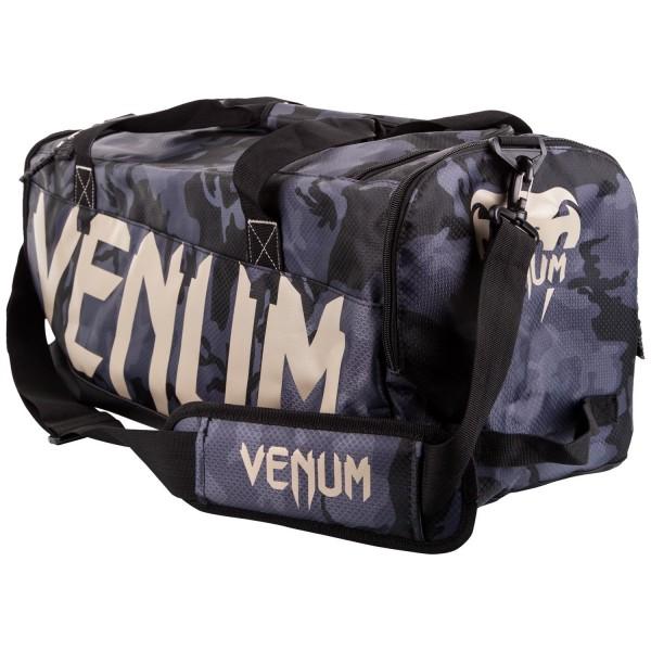 Сумка Venum Sparring Dark Camo VenumСпортивные сумки и рюкзаки<br>Сумка Venum Sparring - Black/White разработана для спортсменов всех направлений, желающих иметь вместительную, стильную и надежную сумку. Идеально подходит для большого количества экипировки. Особенности:- 100% полиэстер- главный отсек вмещает защиту голени и перчатки одновременно- отдельные боковые карманы- ручки и плечевой ремень- размеры 68 х 33 х26 см- сделано в Китае<br>