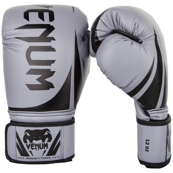 Перчатки боксерские Venum Challenger 2.0 Grey/Black, 12 унций VenumБоксерские перчатки<br>Доступные, но без ущерба качеству, боксерские перчатки Venum Challenger 2. 0, разработанные в Тайланде - идеальный выбор для обучения ударной технике!Благодаря тройному слою пены и широкому ремню, достигается оптимальная степень защиты. Состоят из премиумной полиуретановой кожи (PU) - очень прочные и по отличной цене!Технические характеристики:Из высококачественнойсинтетической кожиТройная плотность пены, для лучшей защиты. 100% полное прилегание большого пальца. Большая упругая липучка для лучшей фиксацииРельефный логотип Venum<br>