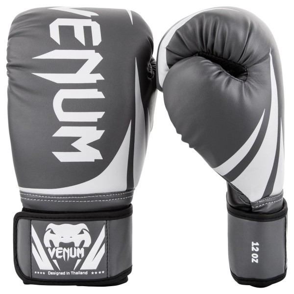 Перчатки боксерские Venum Challenger 2.0 Grey/White/Black, 12 унций VenumБоксерские перчатки<br>Доступные, но без ущерба качеству, боксерские перчатки Venum Challenger 2. 0, разработанные в Тайланде - идеальный выбор для обучения ударной технике!Благодаря тройному слою пены и широкому ремню, достигается оптимальная степень защиты. Состоят из премиумной полиуретановой кожи (PU) - очень прочные и по отличной цене!Технические характеристики:Из высококачественнойсинтетической кожиТройная плотность пены, для лучшей защиты. 100% полное прилегание большого пальца. Большая упругая липучка для лучшей фиксацииРельефный логотип Venum<br>