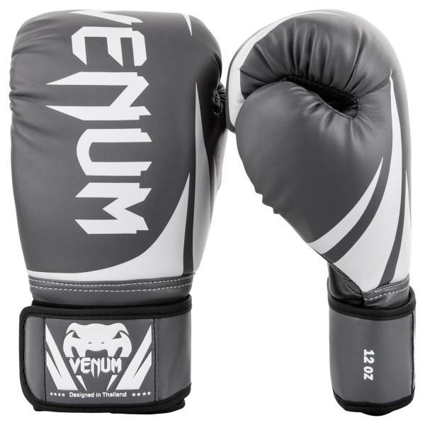 Перчатки боксерские Venum Challenger 2.0 Grey/White/Black, 14 унций VenumБоксерские перчатки<br>Доступные, но без ущерба качеству, боксерские перчатки Venum Challenger 2. 0, разработанные в Тайланде - идеальный выбор для обучения ударной технике!Благодаря тройному слою пены и широкому ремню, достигается оптимальная степень защиты. Состоят из премиумной полиуретановой кожи (PU) - очень прочные и по отличной цене!Технические характеристики:Из высококачественнойсинтетической кожиТройная плотность пены, для лучшей защиты. 100% полное прилегание большого пальца. Большая упругая липучка для лучшей фиксацииРельефный логотип Venum<br>