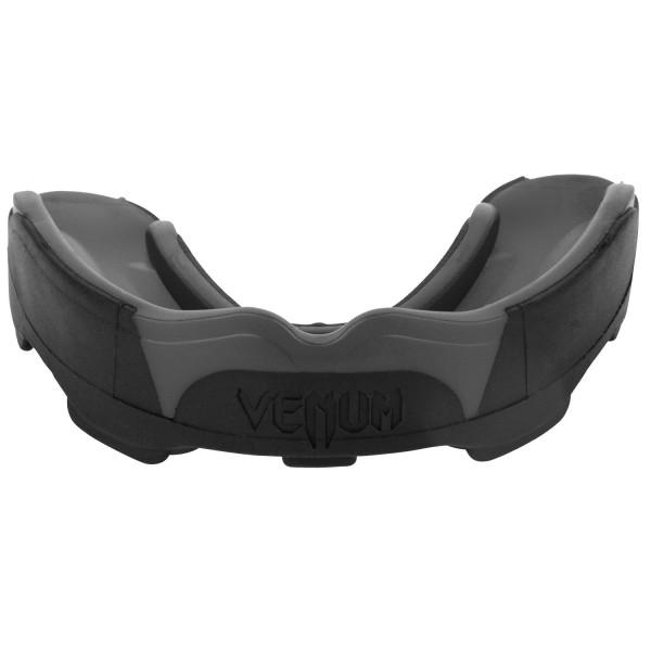 Капа боксерская Venum Predator Black/Black VenumБоксерские капы<br>Капа боксерская Venum Predator Black/Black- новый эталон среди кап в сочетании с идеальной посадкой, гибкостью и высокой защитой. Усовершенствованная форма обеспечивает максимально четкую посадку на зубы, в то время как низкопрофильных дизайн облегчает дыхание и позволяет говорить со спарринг-партнером или тренером. Двухъядерный дизайн дает интеллектуальную защиту от удара: сначала поглощает наиболее мощную часть удара, а затем рассеивает ударную волну в направлении наиболее крепких частей вашей челюсти. Для того, чтобы соответствовать ожиданиям каждого бойца, капа Хищник была разработана в сотрудничестве с лучшими бойцами UFC, а именно Жозе Альдо и Лиото Мачида. Характеристики:- гелевый слой Nextfit для точной посадки и комфорта- многослойная конструкция дает отличную амортизацию удара- специальная форма, обеспечивающая оптимальное дыхание во время тренировок или соревнований- специальный футляр в комплекте- испытано и используется бойцами UFC<br>