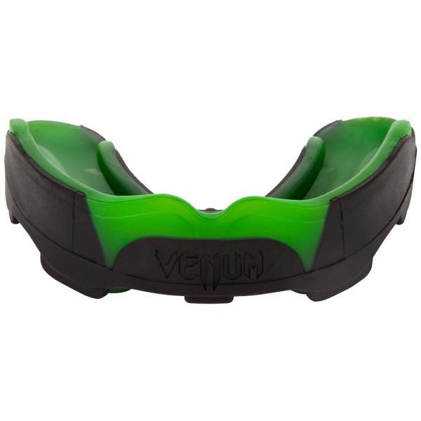 Капа боксерская Venum Predator Black/Green VenumБоксерские капы<br>Капа боксерская Venum Predator Black/Green- новый эталон среди кап в сочетании с идеальной посадкой, гибкостью и высокой защитой. Усовершенствованная форма обеспечивает максимально четкую посадку на зубы, в то время как низкопрофильных дизайн облегчает дыхание и позволяет говорить со спарринг-партнером или тренером. Двухъядерный дизайн дает интеллектуальную защиту от удара: сначала поглощает наиболее мощную часть удара, а затем рассеивает ударную волну в направлении наиболее крепких частей вашей челюсти. Для того, чтобы соответствовать ожиданиям каждого бойца, капа Хищник была разработана в сотрудничестве с лучшими бойцами UFC, а именно Жозе Альдо и Лиото Мачида. Характеристики:- гелевый слой Nextfit для точной посадки и комфорта- многослойная конструкция дает отличную амортизацию удара- специальная форма, обеспечивающая оптимальное дыхание во время тренировок или соревнований- специальный футляр в комплекте- испытано и используется бойцами UFC<br>