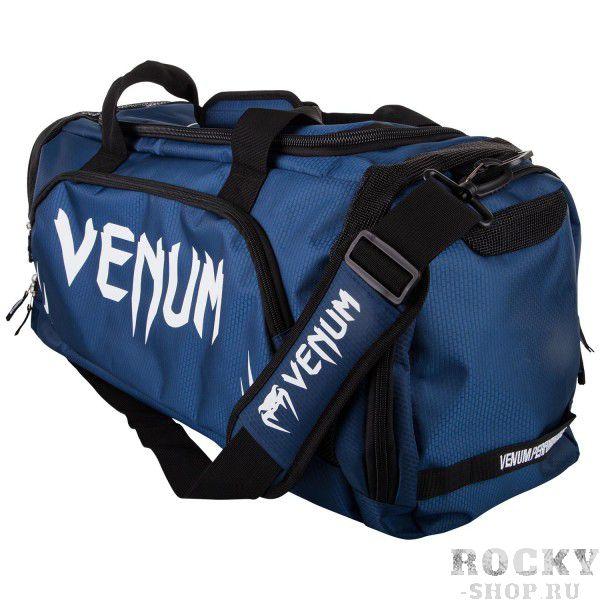 Сумка Venum Trainer Lite Navy Blue/White VenumСпортивные сумки и рюкзаки<br>Новая уникальная многофункциональная сумка от Venum, прекрасно подойдёт для переноски любой тренировочной экипировки. Много удобных карманов и отделений, украшена логотипом Venum. Состоит из специальных сетчатых панелей, которые обеспечивают хорошую вентиляцию, что минимизирует концентрацию запахов и микробов. Очень удобная и практичная, всегда пригодится. Технические характеристики:Большая вместимость для всего необходимогоОтдельный боковой карманРегулируемый мягкий плечевой ременьРазмер: 680 x 330 x 260 ммОбъем: 63 литра<br>