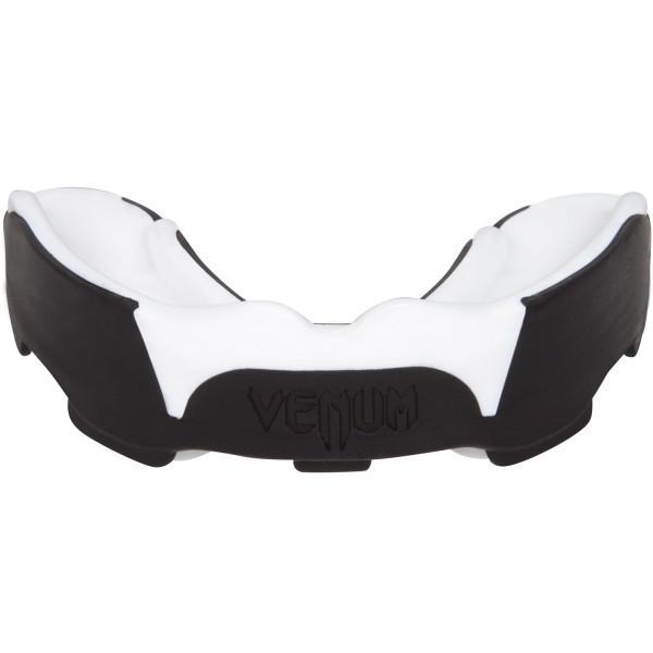 Капа боксерская Venum Predator Mouthguard Black/White VenumБоксерские капы<br>Капа Venum Predator Mouthguard - новый эталон среди кап в сочетании с идеальной посадкой, гибкостью и высокой защитой. Усовершенствованная форма обеспечивает максимально четкую посадку на зубы, в то время как низкопрофильных дизайн облегчает дыхание и позволяет говорить со спарринг-партнером или тренером. Двухъядерный дизайн дает интеллектуальную защиту от удара: сначала поглощает наиболее мощную часть удара, а затем рассеивает ударную волну в направлении наиболее крепких частей вашей челюсти. Для того, чтобы соответствовать ожиданиям каждого бойца, капа Хищник была разработана в сотрудничестве с лучшими бойцами UFC, а именно Жозе Альдо и Лиото Мачида. Характеристики:гелевый слой Nextfit для точной посадки и комфортамногослойная конструкция дает отличную амортизацию удараспециальная форма, обеспечивающая оптимальное дыхание во время тренировок или соревнованийспециальный футляр в комплектеиспытано и используется бойцами UFCСЕ сертификация<br>