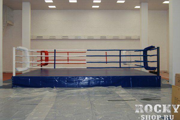 Боксерский ринг на помосте, высота 0,3 м, 6х6 метров Завод спортивного оборудованияОборудование для залов и клубов<br>Соответствуют стандартам соревновательных и тренировочных рингов любительской (AIBA) и профессиональных боксерских федерации. &amp;nbsp;Прекрасно подходит для проведения тренировок и соревнований по боксу и другим видам единоборств. При желании его можно установить и на улице, даже и на не очень ровной поверхности, компенсировать которую можно регулировками помоста, в этом его большое преимущество перед напольными рингами. Основой ринга служит ферма собираемая из металлических рам, скрепленных между собой болтами. Поверх фермы устанавливаются листы фанеры, они же и образуют полбоксерского ринга. На фанеру укладываются листы мягкого настила из матов&amp;nbsp;ППЭ&amp;nbsp;толщиной 2-3 мм и накрываются покрытием из&amp;nbsp;ПВХ. Комплектация - стойки, ферма подиума, настил фанерный, настил ПВВ или ППЭ, покрывало (имп. антискользящее ПВХ), угловые подушки, канаты в чехлах, перемычки, растяжки канатов, защита растяжек канатов, крепеж. <br>Помост 6х6 м, высота 0,3 м, боевая зона 5х5 м. <br><br>Гарантия 1 год<br>