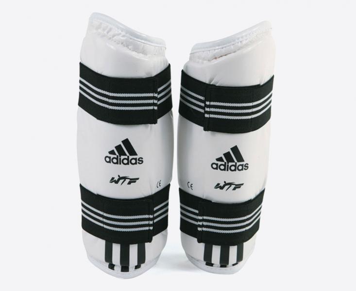 Защита предплечья для тхэквондо WTF Forearm Protector, белая AdidasЭкипировка для Тхэквондо<br>Защита предплечья для тхэквондо WTF и других единоборств.WTF approved. Материал: полиуретан.<br>