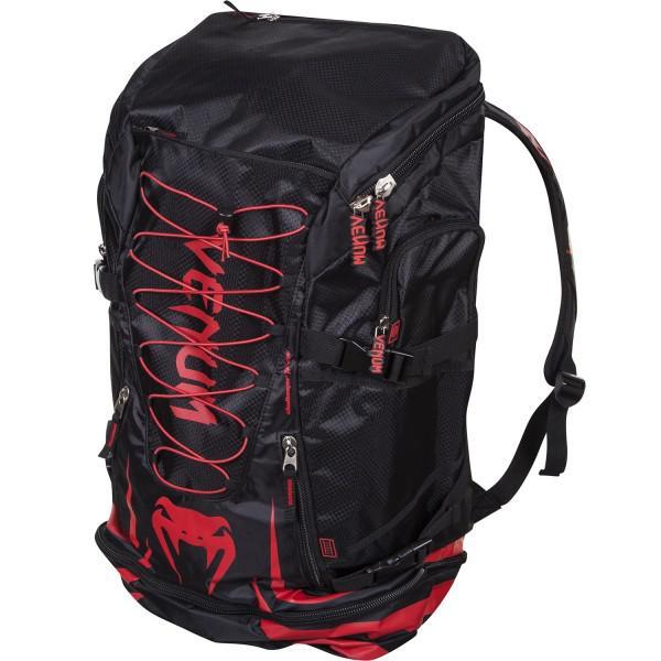 Рюкзак Venum Challenger Xtreme Back Pack - Red Devil VenumСпортивные сумки и рюкзаки<br>Venum Challenger Xtreme Back Pack - Red Devil - не просто рюкзак, это незаменимый спутник любого спортсмена, способный вместить в себя огромное количество одежды и самой габаритной экипировки. Просто закиньте в него все, что у вас есть и отправляйтесь на тренировку. Обратный путь же станет гораздо приятнее, так как ваши вещи будут проветриваться через специальные сетчатые вставки, что препятствует возникновению неприятного запаха и размножению бактерий. Термо-карман сохранит свежесть вашего напитка и сделает его достойной наградой после тяжелой тренировки. Рюкзак оснащен удобными боковыми карманами, флис-карманом, который не позволит вашему мобильному телефону поцарапаться, а также скрытым карманом для мп3-плеера с выводом под наушники. Плечевые ремни регулируются, а в сочетании с эргономичной формой спинки рюкзака снимают нагрузку со спины и плечей. Особенности:Водонепроницаемая тканьБольшое отделение для крупногабаритной экипировкиОбладает дополнительным отделением, которое увеличивает общий размерБоковые карманыФлисовый карман охраняет ваш телефон от царапинСетчатые панелиРегулируемые плечевые ремниРазмер: 350x630x240 сложенный и 350х880х240 разложенныйОбъем: 45 л сложенный и 63 л разложенныйОграниченная серия Red Devil<br>