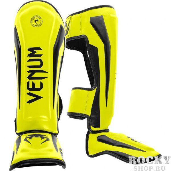 Щитки Venum Elite Neo Yellow VenumЗащита тела<br>Щитки Venum Elite Neo Yellow полностью ручной работы, созданы для того, чтобы обеспечить элитных бойцов лучшей защитой. Сделаны из синтетической кожи , сочетают в себе комфорт и высокую прочность по вменяемой цене. Анатомические крепления на голени и подъеме обеспечивают максимальную защиту и удобство пользования. ОсобенностиПремиум кожа SkintexВысокоплотная пена с дополнительной набивкой в области голени и подъема для повышенной амортизацииЛегкая конструкция обеспечивает неограниченную мобильность и скоростьБольшие застежки-липучки не дадут щиткам прокручиватьсяРельефные логотипыРучная работа, Тайланд<br><br>Размер: L