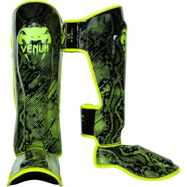 Защита голени Venum Fusion, Зеленая VenumЗащита тела<br>Тайские шингарды (накладки на ноги) Venum Fusion. Данный вид шингард предназначен для особо сильной работы ногами, поэтому они пользуются популярностью у бойцов тайского бокса и K-1. Накладки Venum - идеальное сочетание качества, стиля и комфорта. Шингарды надежно защищают и голень, и стопу! Наполнитель: пена, снижающая силу удара. Внешняя обивка: Semi Leather! Все швы тщательно укреплены. Внутренняя обивка: приятная ткань. Великолепно облегают ногу не создавая какого-либо дискомфорт бойцу. Крепятся с помощью двух ремней-липучек. Сделано в Тайланде, ручная работа! Продаются парой. Данная модель не допускается к оптовой продаже.<br><br>Размер: XL