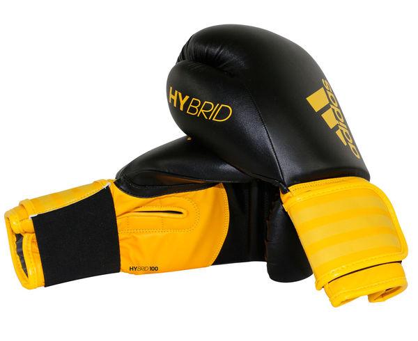 Перчатки боксерские Hybrid 100, 14 унций AdidasБоксерские перчатки<br>Adidas Hybrid 100 ультрановая серия боксерских перчаток. Они изготовлены из полиуретана нового поколения по технологии PU3G INNOVATION. PU3G - этомягкий и прочныйполиуретан, который выглядит, как кожа, и нечувствителен к колебаниям температуры и влажности. ПерчаткаHybrid 100сделана из композитного блока с интегрированным вспененным слоем, придающего перчатке уникальные амортизирующие характеристики. А его эргономичная форма обеспечивает боксеру невероятно удобную посадку перчатки на руке и максимальную безопасность. Перчатка снабжена улучшенной системой липучки для плотной и точной фиксации боксерских перчаток. Крупный логотип adidas и яркая палитра цветов придает перчаткам оригинальный внешний вид. Новыйкомпозитный блокс интегрированным вспененным слоем. Технология PU3GINNOVATION®Оригинальный дизайнИнновационная система закрытияМаксимальная безопасностьПрочная конструкция100% полиуретан.<br><br>Цвет: черно-желтые