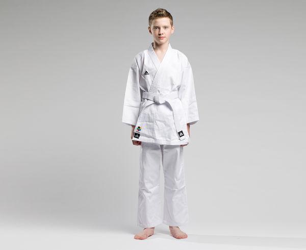 Кимоно для карате Club Climacool WKF белое AdidasЭкипировка для Каратэ<br>Кимоно Adidas Club WKF CLIMACOOL - кимоно сделано из легкого, приятного на ощупь бинарного материала, комбинации смеси полиэстера и хлопка, хлопковые волокна путем укрепления полиэфирными нитями увеличивает свою прочность на растяжение,и долговечность в использовании, а так же позволяет выводит наружу повышенную влажность. Вам и вашему ребенку всегда будет комфортно во время тренировок. КимоноClub WKFодобрено Международной федерацией каратэ(World Karate Federation). Подходит, как для начинающих, так и для продвинутых спортсменов. Материал: 60%-хлопок, 40%- полиэстер. Модель состоит из куртки и брюк. Детали: брюки на резинке+кулиска. Материал: 60% хлопок 40% полиэстер. *Кимоноидет без пояса. Пояс продается отдельно.  Одобрено Международной федерацией каратэ(World Karate Federation)Пояс на штанах на резинке +кулиска. Лёгкая, гибкая и прочная ткань. Материал: 60%- хлопок, 40%- полиэстер.<br><br>Размер: 140 см