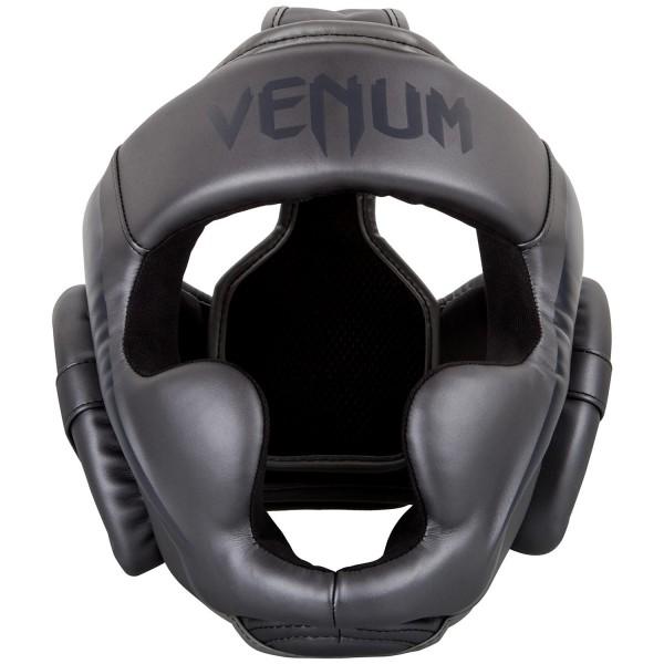 Боксерский шлем Venum Elite, темно-серый VenumБоксерские шлемы<br>Боксерский шлем Venum Elite. Очень мягкая, приятная тканевая подкладка. Рисунок на липучке сделан методом штамповки. Специальный наполнитель(пена) обеспечивает максимальную амортизацию при ударе, а соответственно защищает лицо(голову). Помимо защиты самой головы, шлем так же защищает щеки и уши. Размер универсальный. Крепление - двойная застежка на задней части шлема. Полная защита головы, скул, ушей. Внешняя обивка: Premium Skintex Leather! Сделано в Тайланде.<br><br>Размер: 0