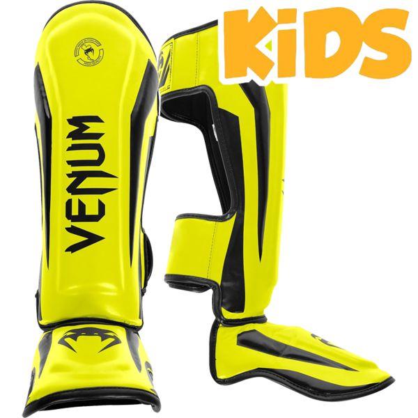 Детские шингарды Venum Elite, yellow black VenumЗащита тела<br>Детские тайские шингарды (накладки на ноги) Venum Elite. Данный вид шингард предназначен для особо сильной работы ногами, поэтому они пользуются популярностью у бойцов тайского бокса и K-1. Накладки Venum - идеальное сочетание качества, стиля и комфорта. Шингарды надежно защищают и голень, и стопу! Наполнитель: пена, снижающая силу удара. Внешняя обивка: смесь натуральной кожи КРС и Premium Skintex leather! Все швы тщательно укреплены. Внутренняя обивка: приятная ткань. Великолепно облегают ногу не создавая какого-либо дискомфорт бойцу. Крепятся с помощью двух ремней-липучек. Шингарды очень легкие в сравнении с аналогами других производителей. Сделано в Тайланде, ручная работа! Продаются парой.<br><br>Размер: M