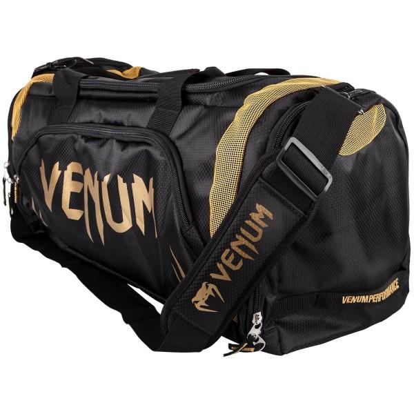 Сумка Venum Trainer Lite Black/Gold VenumСпортивные сумки и рюкзаки<br>Новая уникальная многофункциональная сумка от Venum, прекрасно подойдёт для переноски любой тренировочной экипировки. Много удобных карманов и отделений, украшена логотипом Venum. Состоит из специальных сетчатых панелей, которые обеспечивают хорошую вентиляцию, что минимизирует концентрацию запахов и микробов. Очень удобная и практичная, всегда пригодится. Технические характеристики:Большая вместимость для всего необходимогоОтдельный боковой карманРегулируемый мягкий плечевой ременьРазмер: 680 x 330 x 260 ммОбъем: 63 литра<br>