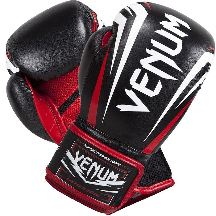 Боксерские перчатки Venum Sharp, 16 oz VenumБоксерские перчатки<br>Боксерские перчатки Venum Sharp. Эта новинка не оставит равнодушным никого - представляем новые боксерские перчатки от Venum ручной работы. Качество этой новинки просто поражает - отлично обработанные швы, идеально подогнанные друг к другу части перчаток, удобные манжеты, края которых также отстрочены кожей - все это ставит перчатки Шарп в одну линейку с самыми популярными профессиональными моделями. Нужно подчеркнуть, что перчатки сделаны из кожи Nappa. Внутри перчатки наполнены трехслойной анатомической пеной, которая гасит вибрацию от ударов и не дает рукам травмироваться. Защита рук стала бесперецедентной. Также стоит отметить, что в этой модели специалисты Venum отдельно продумали систему фиксации и петель - теперь перчатки сидят как никогда плотно и удобно. При этом внутренняя конструкция и используемые материалы еще лучше отводят влагу. А антибактериальная пропитка не позволит запахам распространиться по всему помещению, в котором вы храните свою экипировку. Большой палец на перчатках зафиксирован - забудьте о возможном скручивании или травмах. Запястье также крепко фиксируется манжетой. Перчатки украшены рельефной эмблемой Venum. Сделаны вручную в Таиланде.<br>